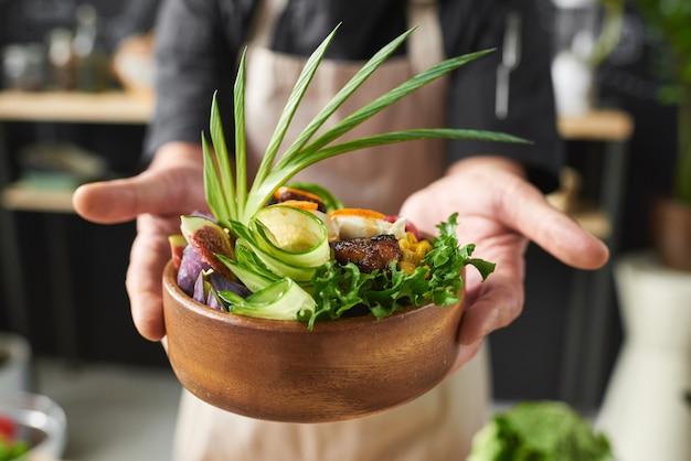 Close-up van de schotel van de kokholding met vlees dat met groenten en slablaadjes wordt verfraaid