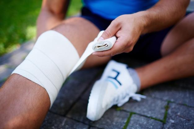 Close-up van de sporter met knie verstuiking
