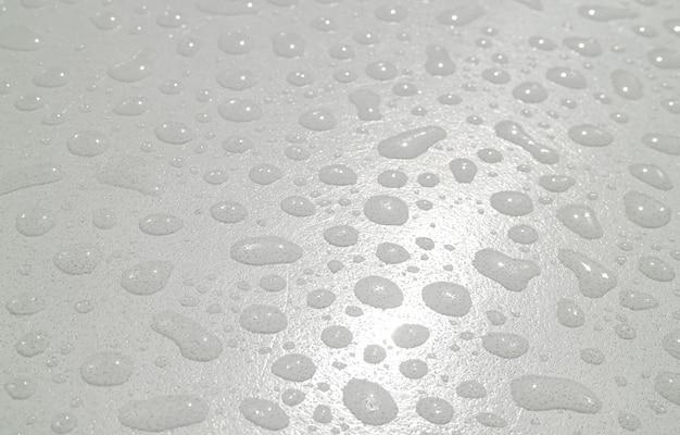 Close-up van de textuur van waterdruppeltjes op het acryl tafelblad na de regen