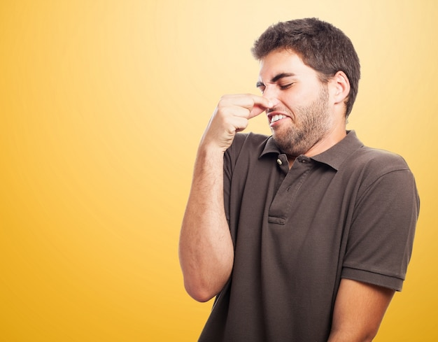 Close-up van de tiener met bruin t-shirt bedrijf zijn neus
