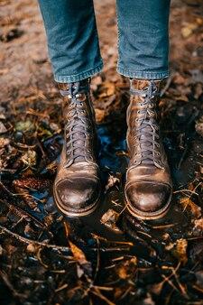 Close-up van de uitstekende oude gekraste laarzen van mensen` s benen die zich in vulklei bevinden.
