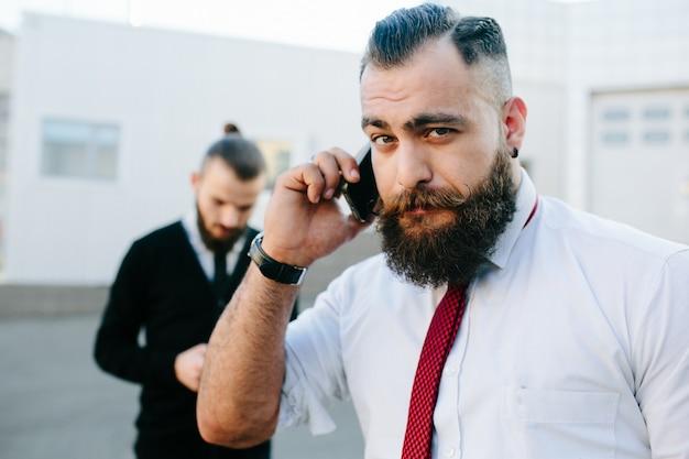 Close-up van de uitvoerende met baard praten aan de telefoon