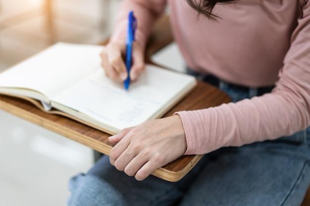 Close-up van de universiteitsstudenten die een notitie schrijven op een notitieboekje in de klas terwijl ze luisteren en de lezing bestuderen. close up van de handen van de vrouw schrijven op kladblok geplaatst op houten bureaublad