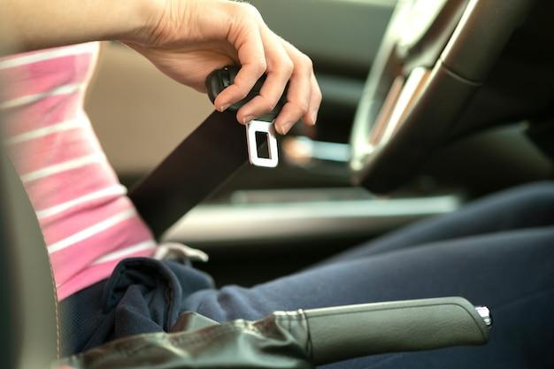 Close-up van de veiligheidsgordel van de vrouwenhand tijdens het zitten in een auto voor veiligheid alvorens op de weg te rijden