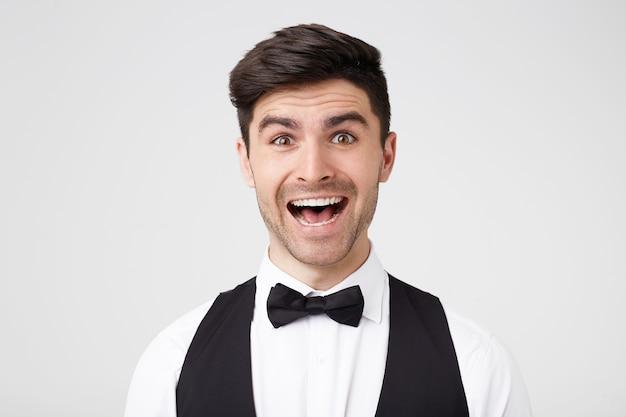 Close-up van de verbaasde aantrekkelijke jonge man in zwarte vlinderdas kijkt frontaal met een brede, verbaasde glimlach