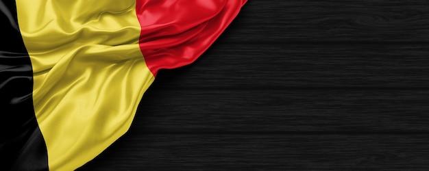 Close up van de verenigde staten van belgische vlag op de zwarte houten achtergrond 3d render