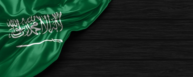 Close up van de verenigde staten van saoedi-arabië vlag op de zwarte houten achtergrond 3d render