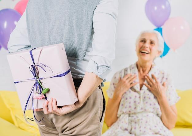 Close-up van de verjaardags gift van de mensen verbergende verrassing van zijn gelukkige vrouw