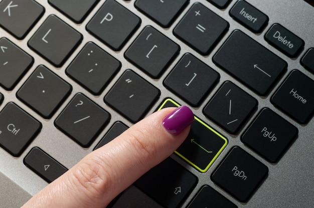 Close-up van de vinger van de vrouw op enter-knop te drukken