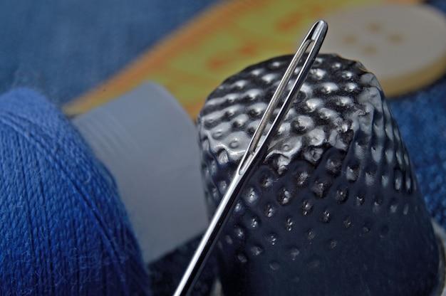 Close-up van de vingerhoed van een spoel met draden en naalden.