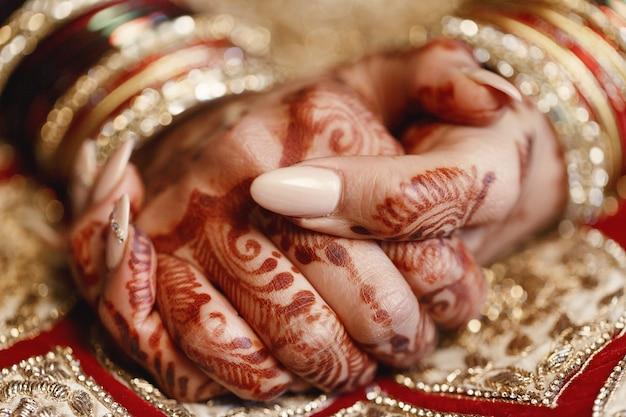 Close-up van de vingers van de lange bruid bedekt met mehndi en liegen