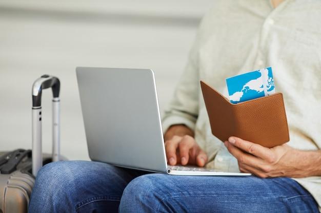 Close-up van de vliegtuigkaartjes die van de mensenholding op laptop computer typen hij de kaartjes online registreert
