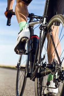 Close-up van de voet van een jonge man die op de weg fietst.