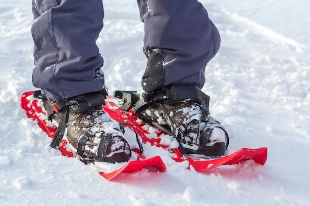 Close-up van de voeten en de benen van de mensenskiër in korte plastic heldere professionele brede skis op witte zonnige sneeuw. actieve levensstijl, extreme wintersport en recreatie.