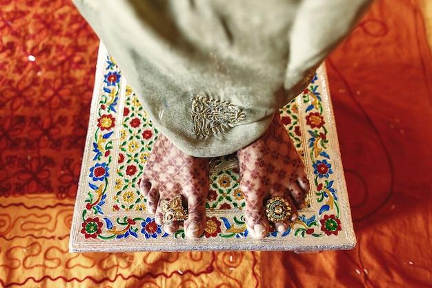 Close-up van de voeten van de bruid bedekt met mehndi en staan