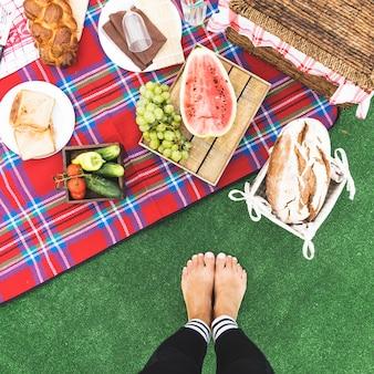 Close-up van de voeten van de vrouw dichtbij de picknicksnack op deken