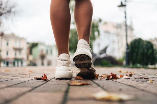Close-up van de voeten van een hardloper die in herfstbladeren loopt en traint voor een marathon en een gezonde levensstijl