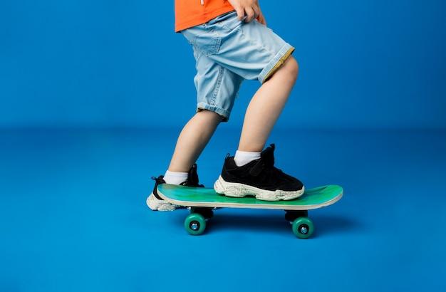 Close-up van de voeten van een kind rijden op een skateboard op een blauwe ondergrond met ruimte voor tekst