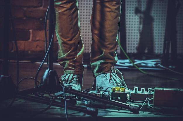 Close-up van de voeten van een persoon in de buurt van gitaarpedalen en een microfoonstandaard onder de lichten