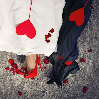 Close-up van de voeten van geliefden en twee rode harten die op hen liggen.