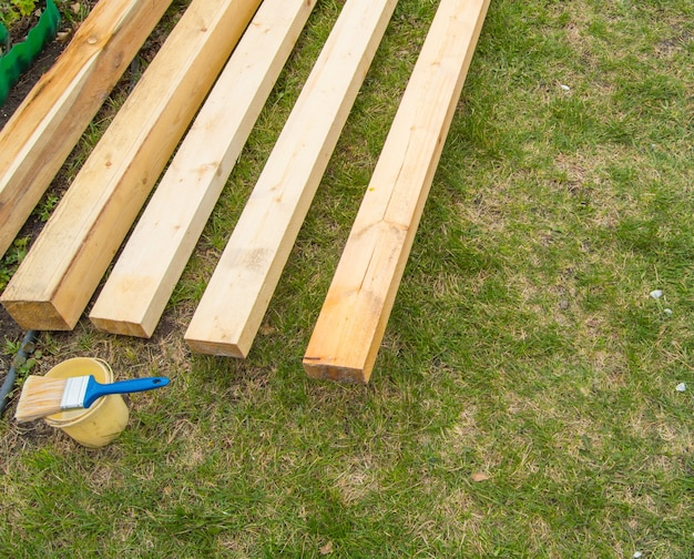 Close-up van de voorbereiding voor het schilderen van nieuwe houten planken die op het gras liggen, naast een blikje verf met een kwast, in de open lucht.