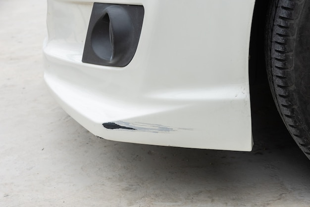 Close-up van de voorkant van de gecrashte auto met scheuren en diepe schade aan de lak