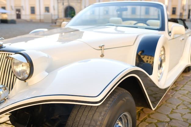 Close-up van de voorkant van een witte vintage auto op de binnenplaats van het kasteel.