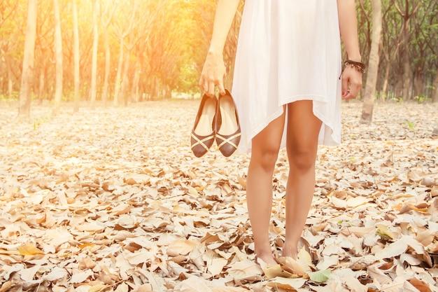 Close-up van de vrouw die haar schoenen in de hand