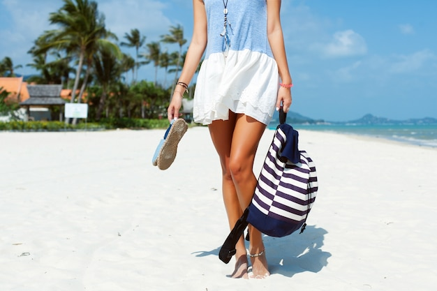 Close-up van de vrouw met haar tas en sandalen op het strand