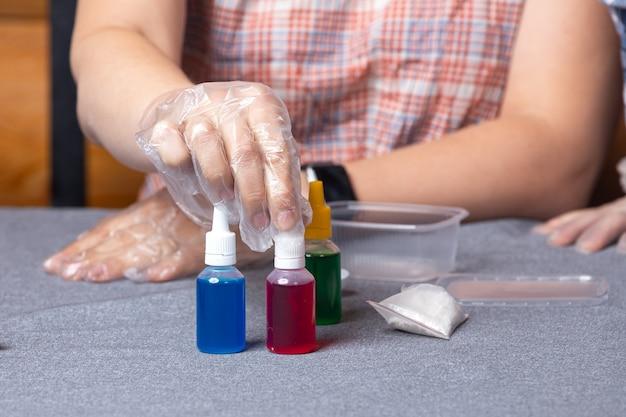Close-up van de vrouwelijke wetenschapper schikken potten met chemische elementen, voor experimenten thuis