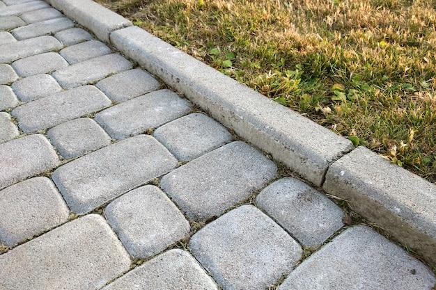 Close-up van de weg van de plaksteen bedekte weg bij park of binnenplaats. het voetpadweg van de gang bij de tuin van de huiswerf.