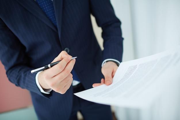 Close-up van de werknemer het lezen van het contract voor ondertekening