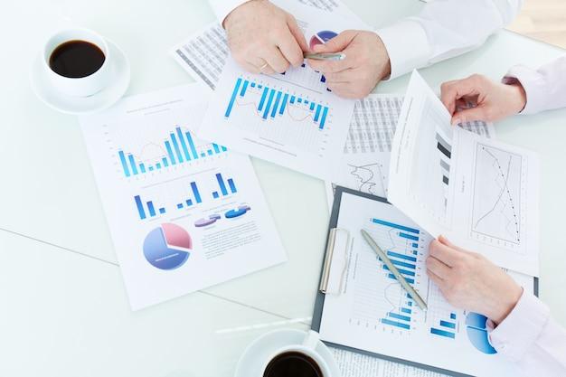 Close-up van de werknemers het analyseren van statistische gegevens