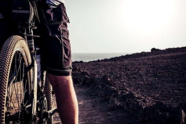 Close-up van de wil van de fiets op een rotsachtig strand stopte met kijken naar het strand voor de zee - actieve senior of volwassene