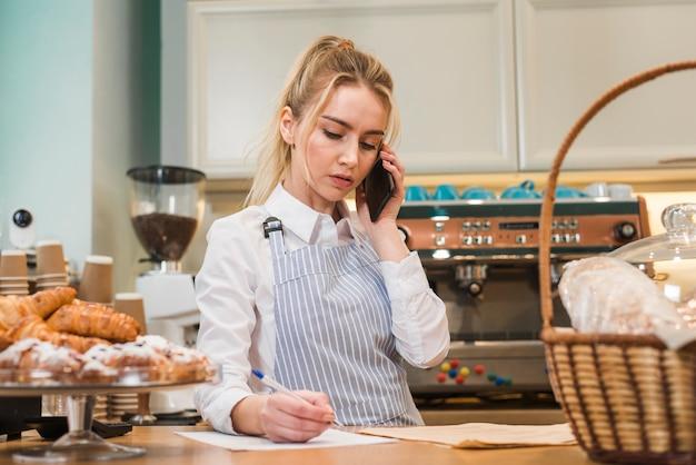 Close-up van de winkeleigenaar die van de blonde jonge bakkerij telefoonbestelling neemt