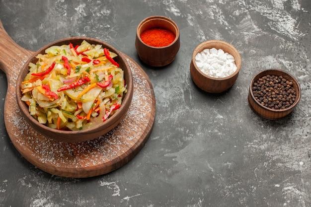 Close-up van de zijaanzicht salade groente salade op de houten bord kommen met kleurrijke specerijen