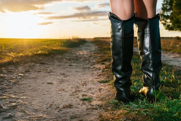 Close-up van de zwarte cowboylaarzen van de vrouw die zich in het veld bij zonsondergang bevinden. ruimte kopiëren.