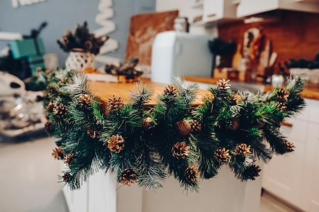 Close-up van decoratieve fir tree takken met dennenappels rond kookeiland in de moderne keuken.