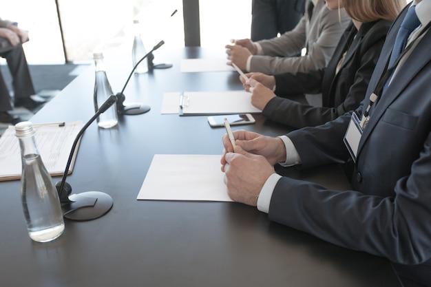 Close-up van deelnemers aan persconferentie die op een rij aan tafel zitten voor publiek