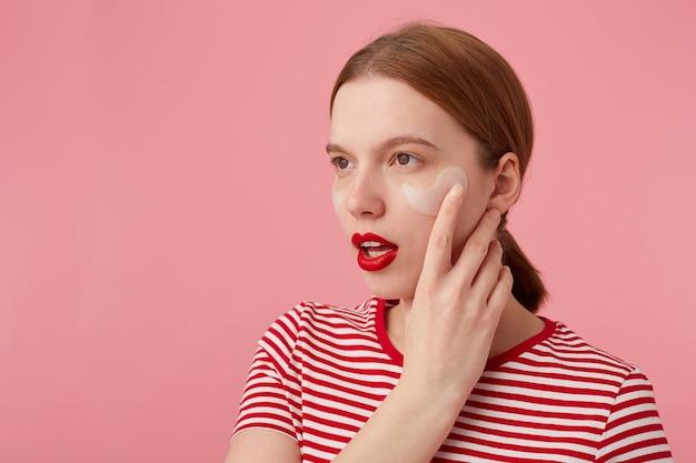 Close-up van denken jong roodharig meisje met rode lippen en met vlekken onder de ogen, draagt in een rood gestreept t-shirt, kijkt weg, raakt de wang, staat.