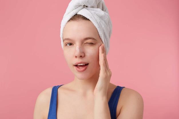 Close-up van denkende jonge vrouw met een handdoek op haar hoofd na het douchen, kan geen beslissing nemen, kijkt en knipoogt, raakt wang, staat.