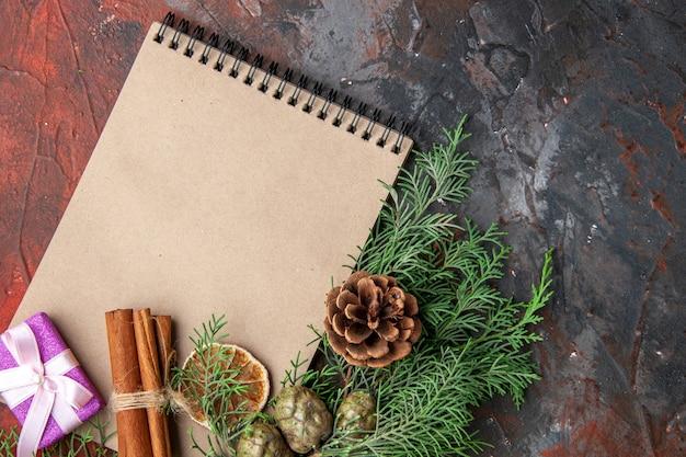Close-up van dennentakken paarse kleur geschenk en gesloten spiraal notebook kaneel limoenen aan de rechterkant op rode achtergrond