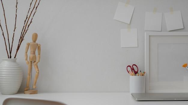Close-up van designer werkruimte met laptop, frame, tekengereedschappen, decoraties en kopie ruimte op witte tafel