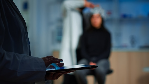 Close up van deskundige wetenschapper in neurologische disfuncties die in het laboratorium staan en aan de tablet werken. medisch onderzoeker die patiënt voorbereidt op hersenscan die elektrische activiteit van zenuwstelsel analyseert