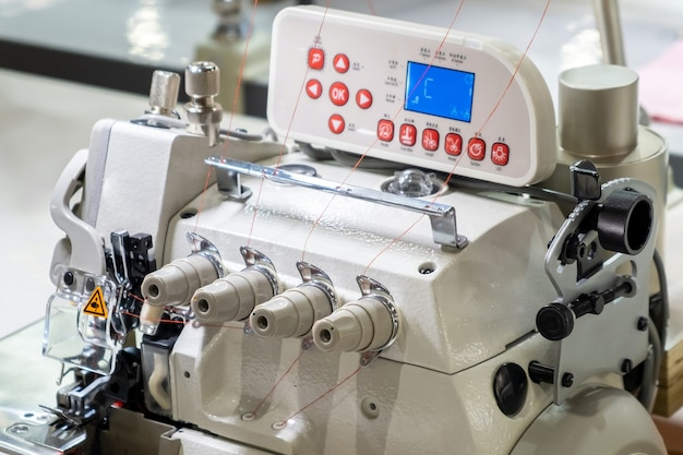 Close-up van details van moderne witte professionele elektrische naaimachine met elektronisch bedieningspaneel op een tafel in de fabriek. werkplaats van naaister. geen mensen.