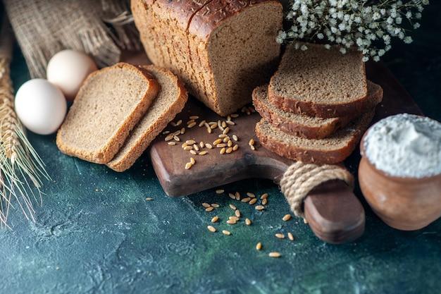 Close-up van dieet zwart brood tarwe op houten snijplank bloem eieren bloem in kom bruine handdoek op blauwe achtergrond
