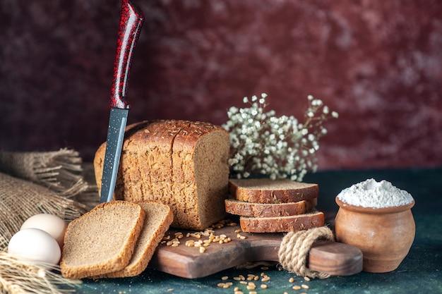 Close-up van dieet zwart brood tarwe op houten snijplank mes bloem eieren meel in kom bruine handdoek op gemengde kleuren achtergrond