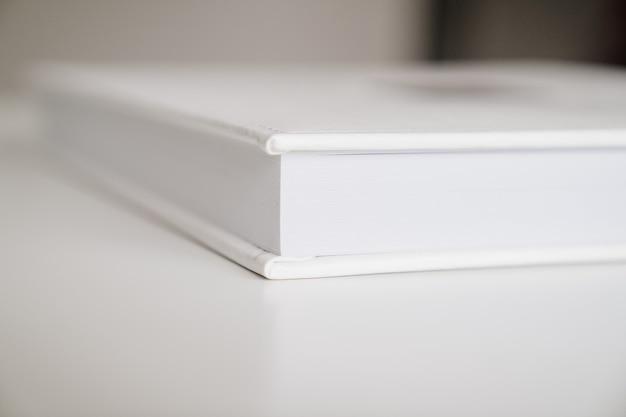 Close-up van dik plastic pagina's wit boek in leerband. print producten. fotoboeken en albums. individuele producten.