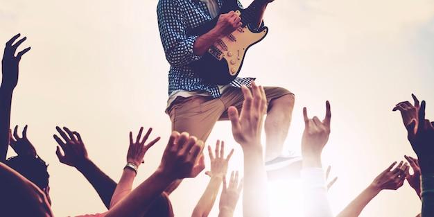 Close-up van diverse armen opgeheven in live muziekconcert
