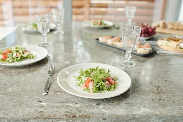 Close-up van diverse kazen en notenhapjes op houten plaat die op eettafel met servet wordt geplaatst